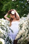 Okouzlující mladá dáma se zvedne hel dlouhé kudrnaté tmavé vlasy na jaře zahrady plné bílé květy