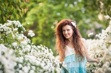 Charming young woman with beautiful smile in spring garden full of white flowers