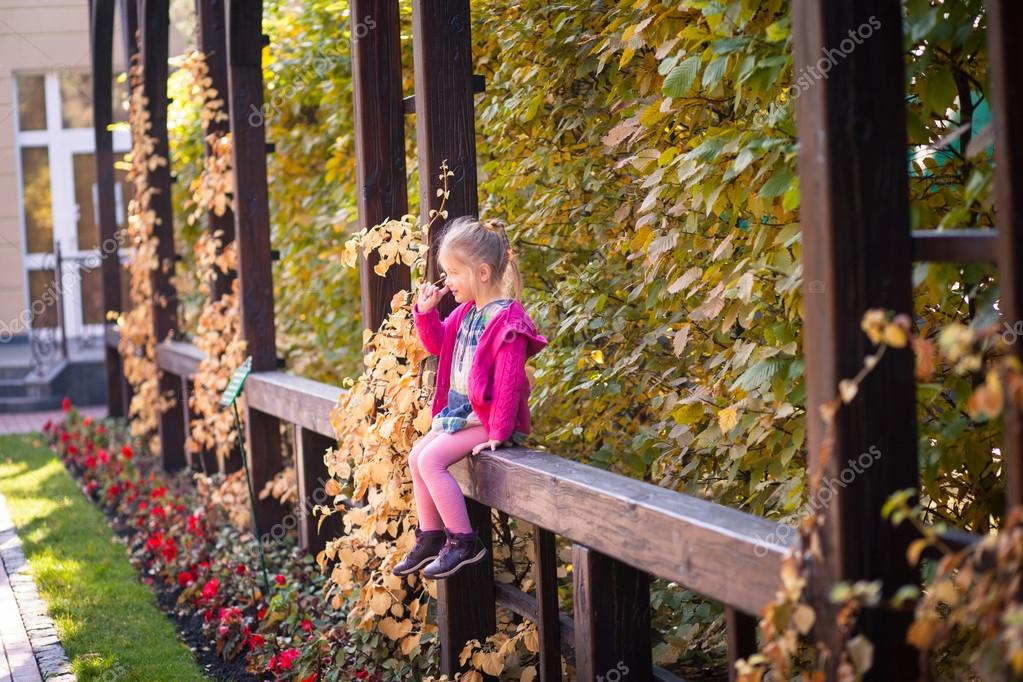 Smiling funny little girl in bright clothes picking her nose