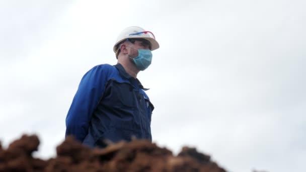 Zaměstnanci v maskách se dívají na zákop u moderního bagru