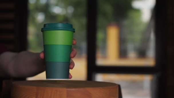 Ügyfél vesz csésze finom kávét kis fa asztal