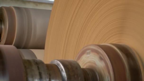 Velký kbelík balicího papíru se otáčí na staré kovové role