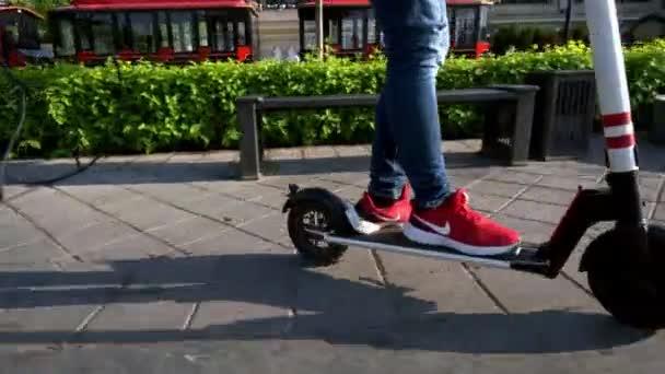 Person in Sportschuhen fährt mit E-Scooter Böschung entlang