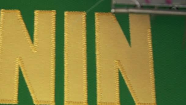Automatické strojové výšivky písmena na uniformě v obchodě