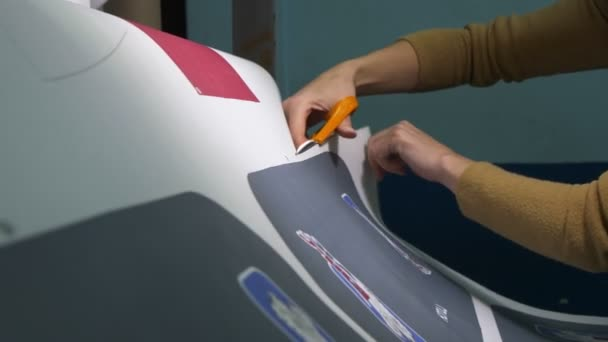 Pracovník stříhá papírový list se vzorkem pro loga hokejového týmu