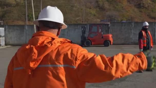 Arbeiter signalisiert Maschinen, die im Hof der Produktionsanlage stehen