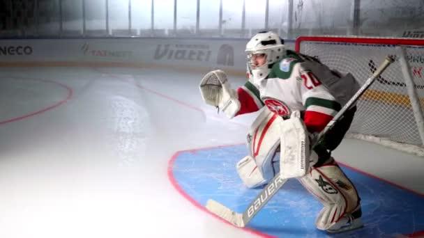 Brankář chytí hokejový puk bránu na kluzišti