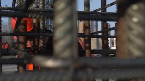 Mitarbeiter in orangefarbener Weste und Helm überprüft Metallkarkasse