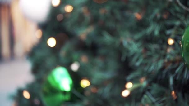 Rozmazané zlaté věnce na vánočním stromečku jako pozadí. Rozostřené rozmazané slavnostní bokeh světla