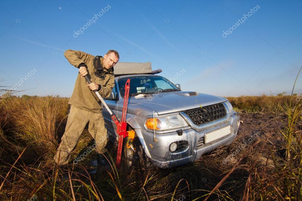 Man lifting car stucked in deep mud by hi jack