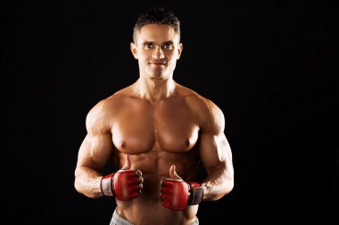 Strong Athletic Man showing muscular body on a black background.Strong Athletic Man showing muscular body.muscular man with boxing gloves on a black background.muscular man wearing gloves for mixed ma