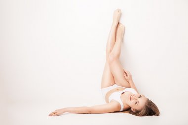 Beautiful woman legs raised up high lying