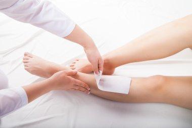 Beautician waxing  woman legs in spa salon