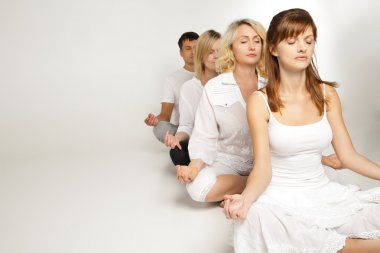 Group of people relaxing and doing yoga in white