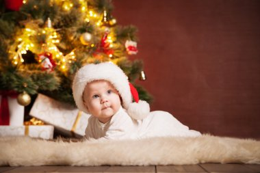 Happy baby wearing Santa hat over christmas tree