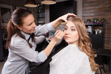 Stylist doing professional make up of young woman
