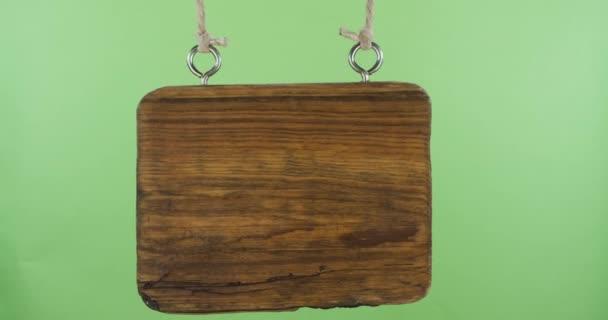 Po stranách se pohupuje stará prázdná dřevěná cedule. Zelená obrazovka.