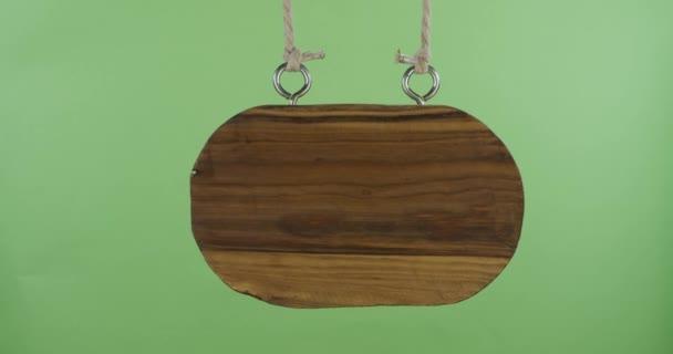 Egy régi ovális fa tábla lóg a kötélen. A hely a design, szöveges hely. Elszigetelt