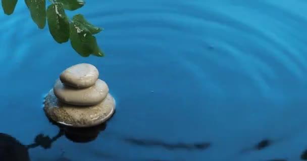 Esik az eső a kék vízbe. Fehér kövekből és zöld levelekből álló piramis a víz felett.