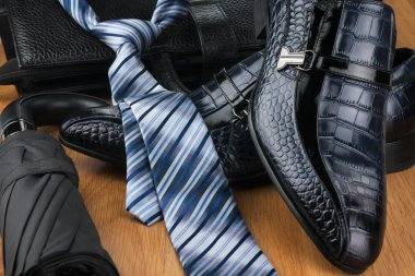 Classic men's shoes, tie, umbrella and bag on the wooden floor