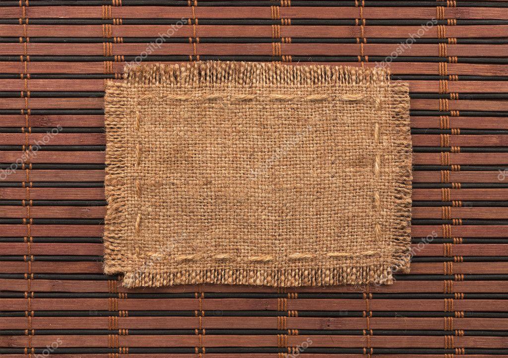 Marco de arpillera, se encuentra sobre un fondo de estera de bambú ...