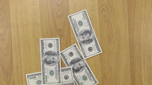 Businessman throws dollars on wooden table, background of money