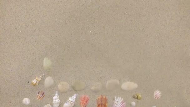 Vítr odfoukne písek z kamenů a mořské mušle, pohled shora