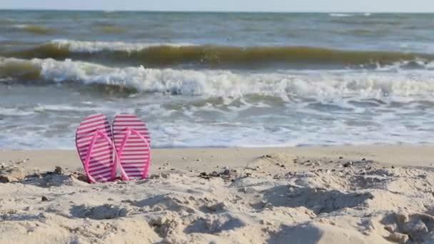 Panorama pink flip flops on yellow sandy beach near sea waves