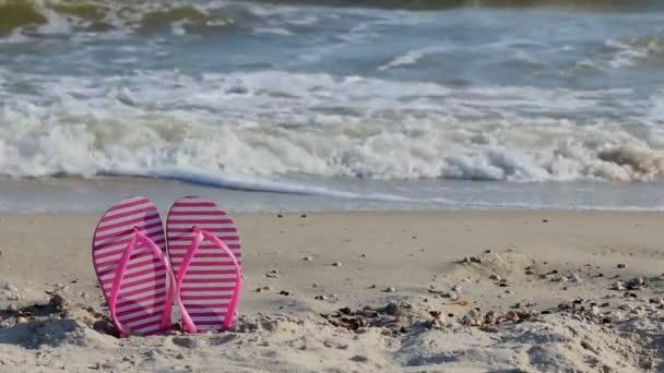 Pink flip papucs a sárga homokos strand közelében a tenger hullámai, senki sem