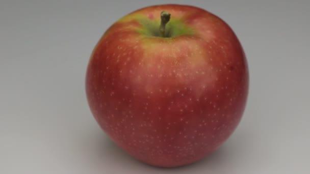 Červené jablko se otáčí kolem své osy.