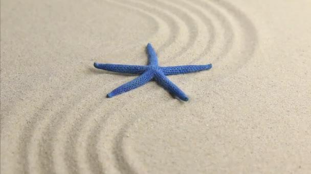 A hullámzó homokos tengerparton kék csillag
