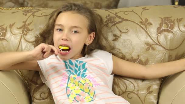 Dívka lízala cukroví na hůl v podobě citron