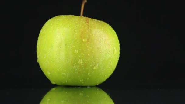 Zöld alma-ben csepp harmat forog a tengelye.