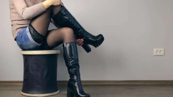 Dívka sedící na pouf sundat ty boty a ukazuje třída