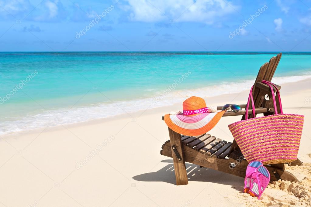 Chair With Bag, Hat, Flip Flops And Sunglasses On Sunny Beach, T
