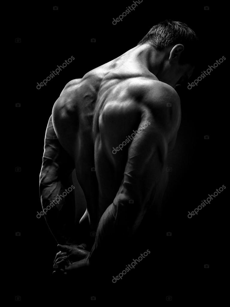 Handsome muscular male model bodybuilder preparing for fitness training turned back studio shot on black background black and white photo