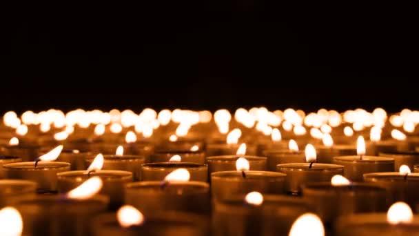 Brennende Kerzen bis zum Horizont. Viele kleine brennende Kerzen ergeben in absoluter Dunkelheit einen feurigen Teppich bis zum Horizont