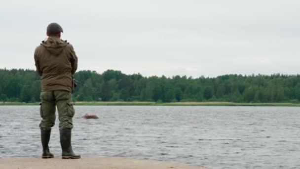 Halászok a tóparton. Felnőtt férfi forgó halászattal áll a mólón az öböl hátterében
