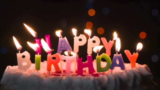 Fluttering Holiday Candles on the Cake. Cake with candles in the form of an inscription Happy Birthday. In the background, flashing and moving lights bokeh in the dark