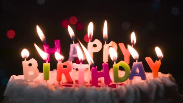 Táncoló gyertyafény a tortán. Torta gyertyákkal felirat formájában Boldog születésnapot. A háttérben villogó és mozgó fények bokeh a sötétben