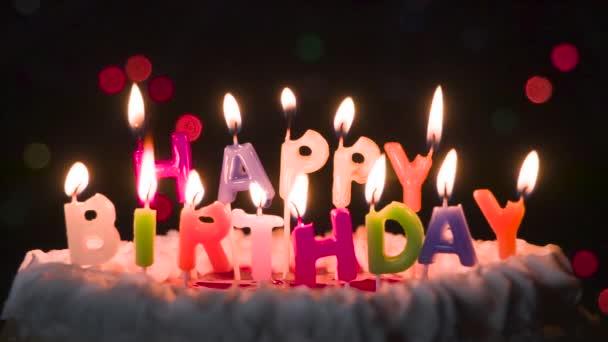 A tortán lévő gyertyák lassan elfújódnak. Torta gyertyákkal felirat formájában Boldog születésnapot. A csillogás a gyertyákon lassan és fokozatosan kialszik.