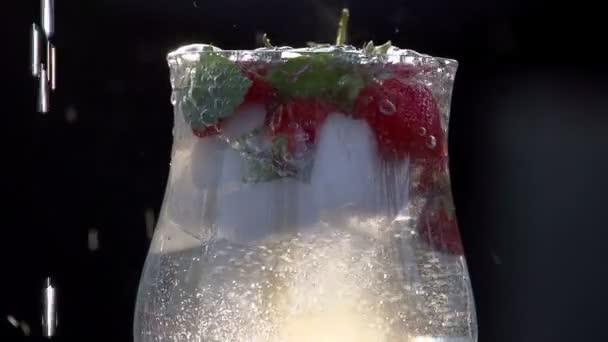 Sklenice čisté studené vody s bobulemi.