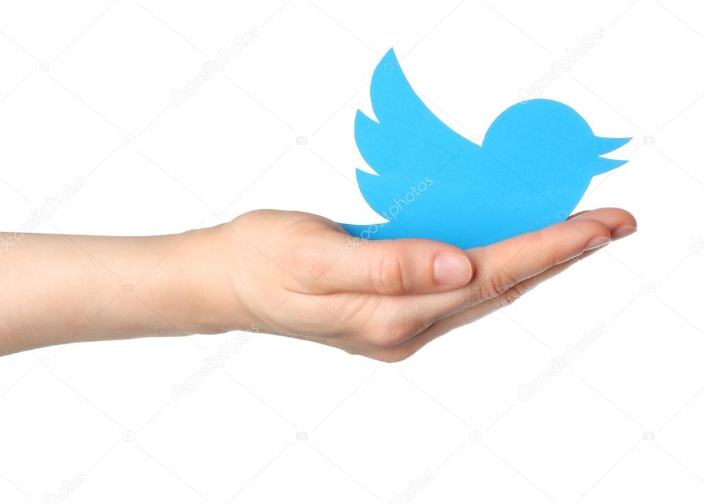 Hand holds twitter logotype bird printed on paper