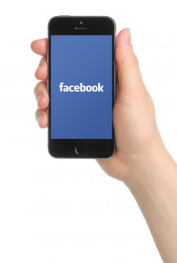 Hand holds iPhone 5s Space Gray with Facebook logo