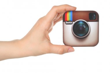 Hand holds Instagram logo printed on paper on white background