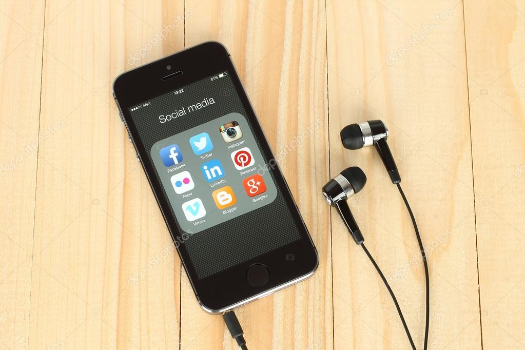 Smart phone with social media logos on its screen and headphones on wooden background