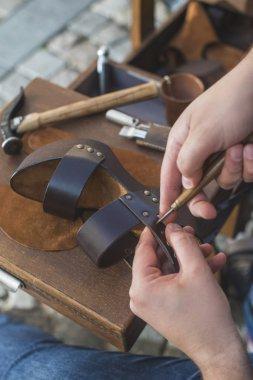 shoemaker's hands making shoes
