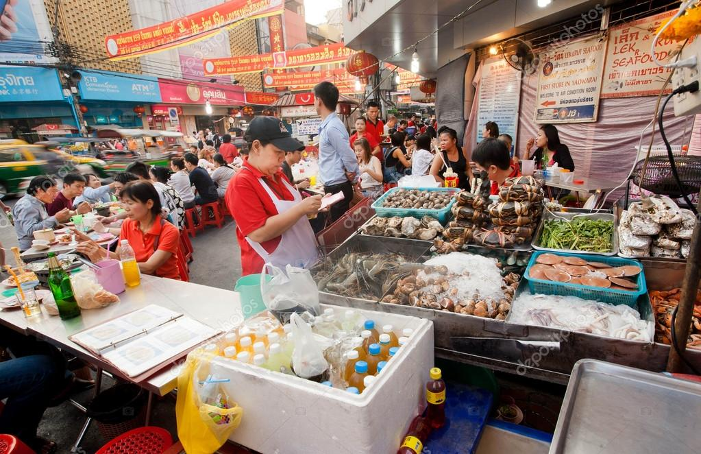 Street trader of seafood market with shrimps, brines, fish and meat