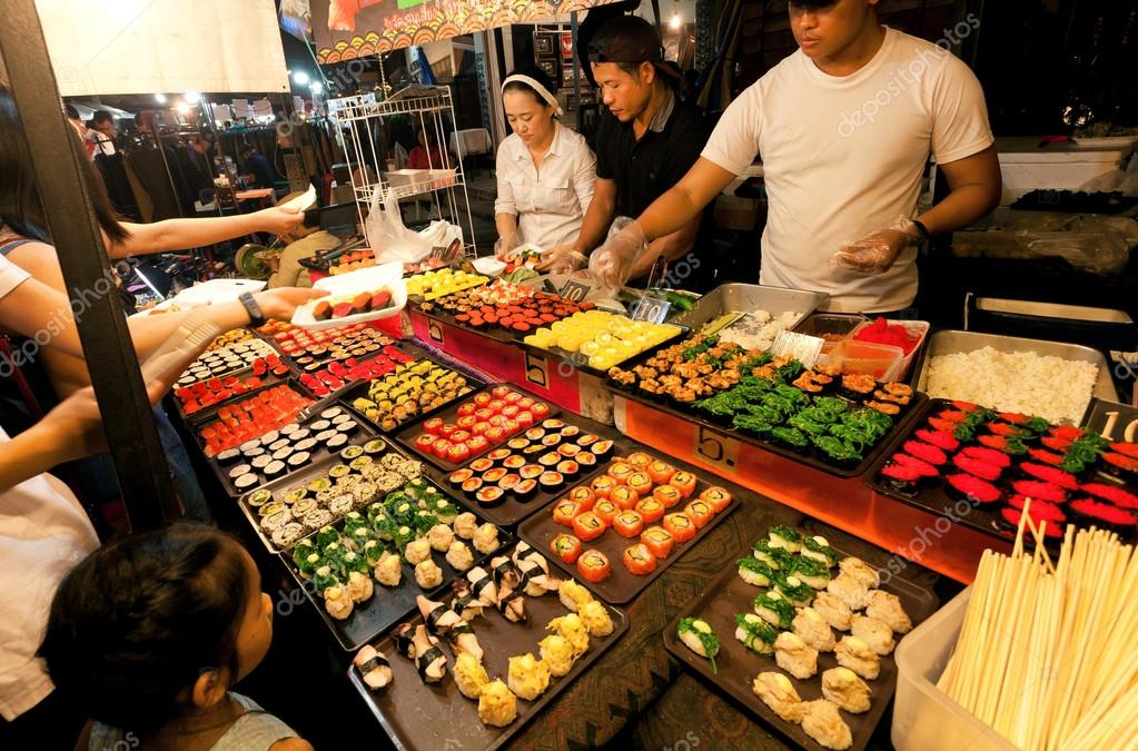 people making choice at sushi stall with seafood delicacies on the