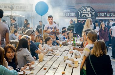 Big table outdoor with eating and drinking people during popular Street Food Festival